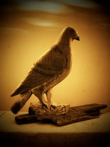 handcrafted wooden dove on a piece of driftwood
