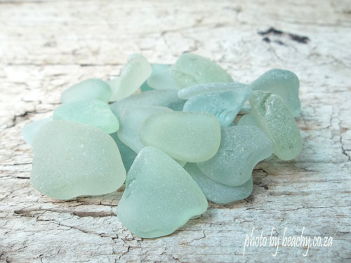 sea foam sea glass pieces on pale wood