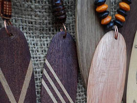 copper jump rings on wood surfboard necklaces