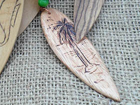 wooden surfboard necklace with palm tree